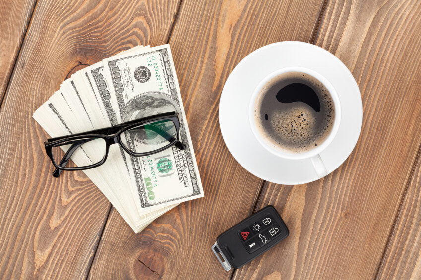 Money cash, glasses, car remote and coffee cup on wooden table