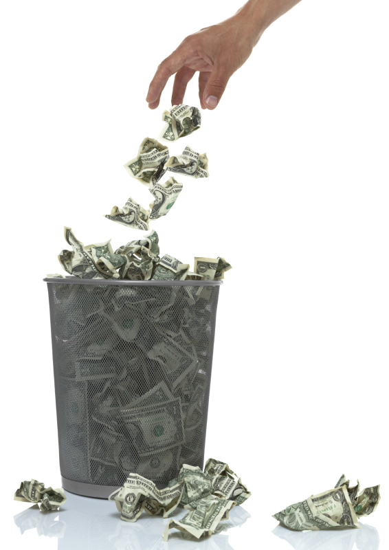Hand throwing money into a trash can